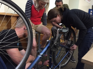 My teamate Andrew took this picture of Nate teaching Robin and I how to detach and reattach the back wheel of a bicycle.  Mark Hines observed our progress.