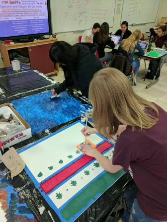 Isabella and Hannah paint the backgrounds for their Desmos artwork.